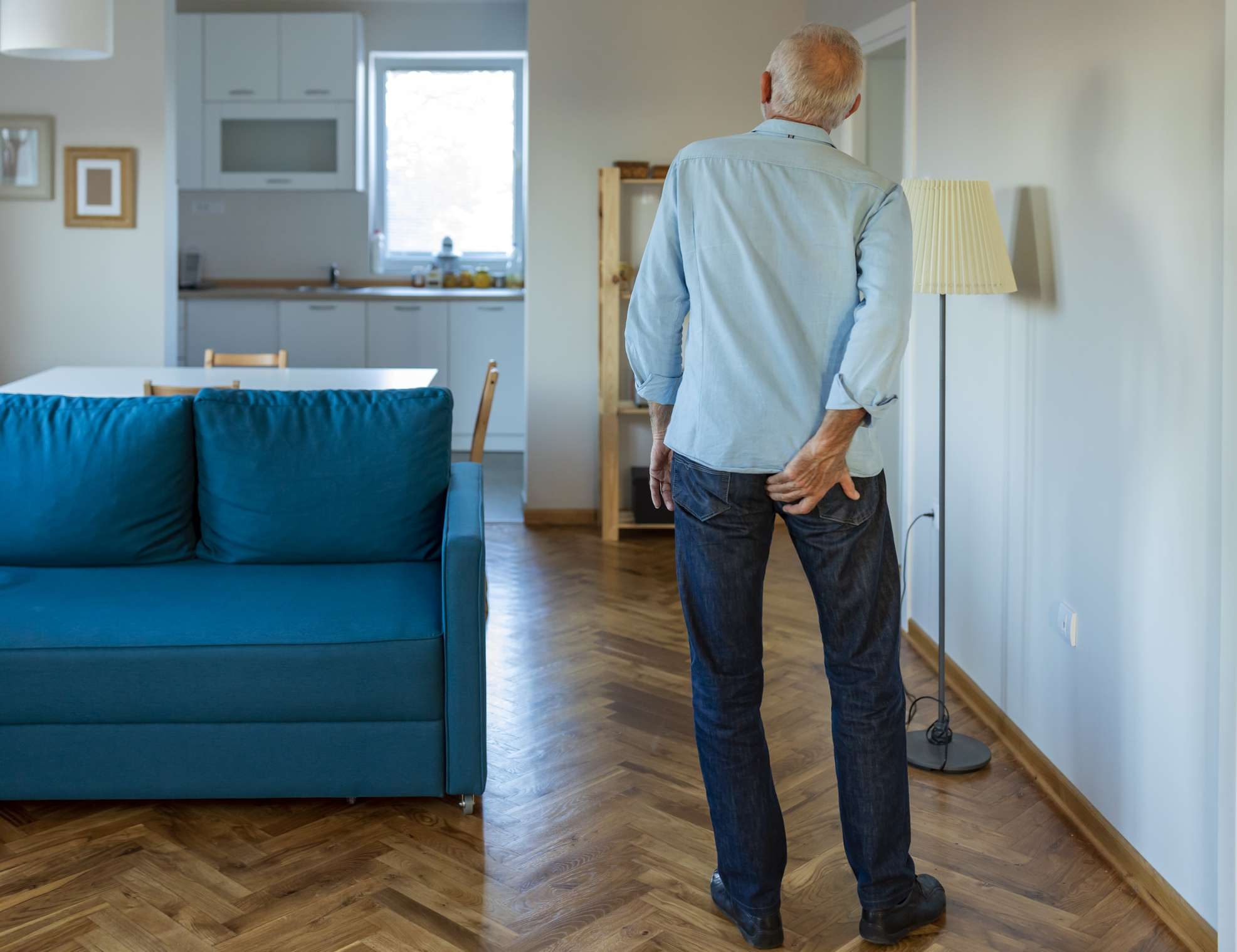 Man with irritated backside walking in his apartment