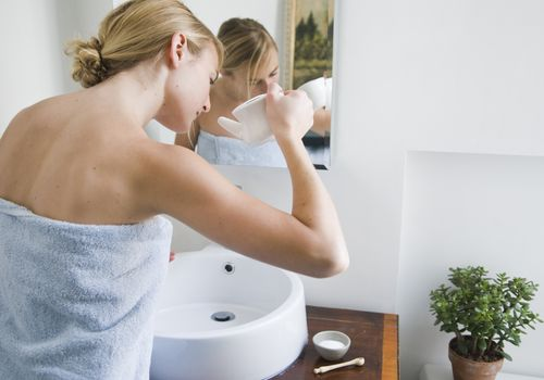 Woman Using a Neti Pot in a bathroom