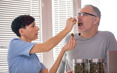 Alternative Healthcare Worker Dropping CBD Oil on Patient's Tongue