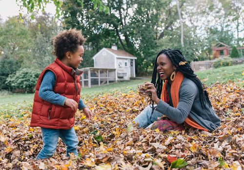 Mother playing with son in pile of leaves