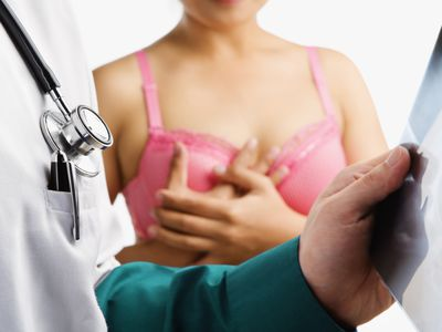 woman with breast cancer and pink bra with doctor checking x-ray looking for metastases