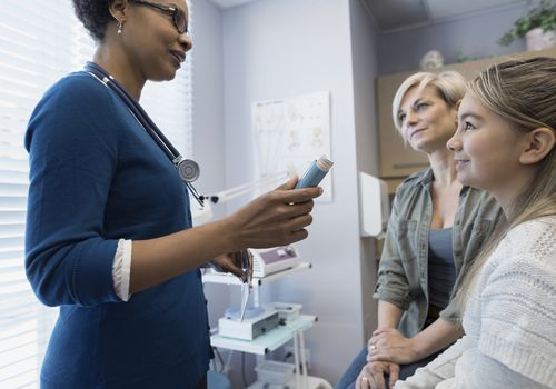 Pediatrician explaining inhaler to patient and mother