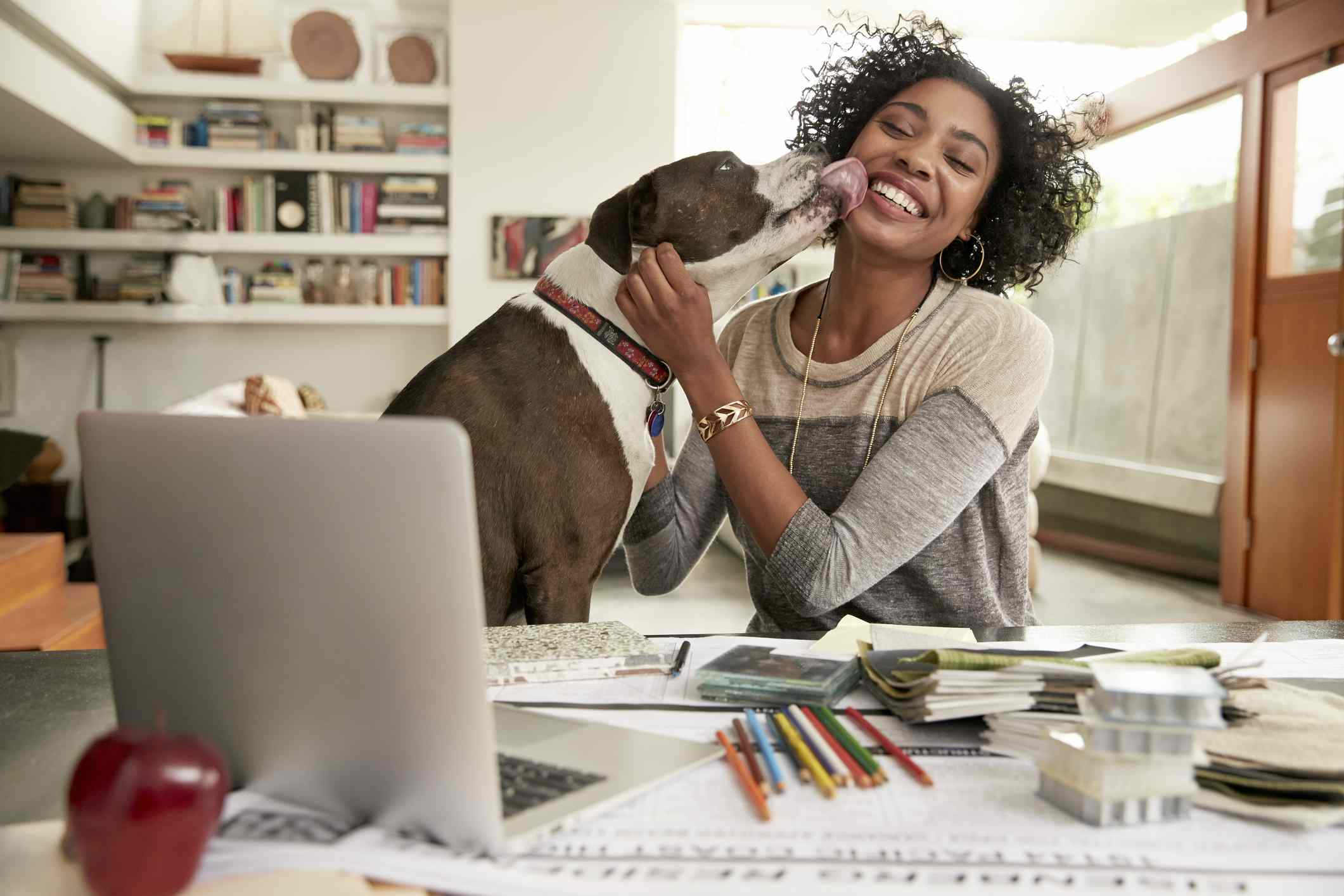 A dog licking the face of a woman at work
