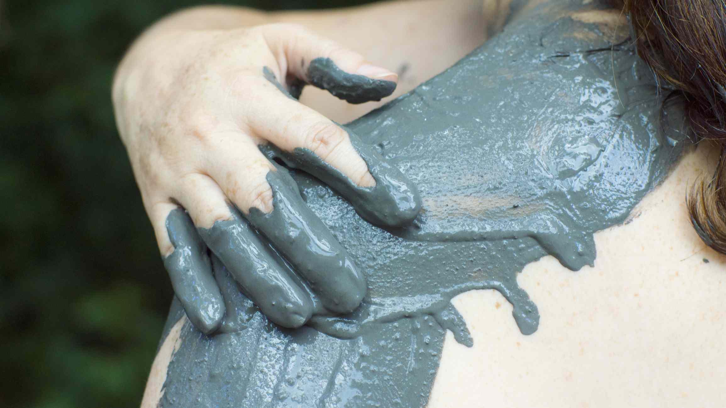 Woman applying mud to shoulder