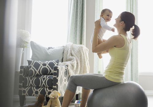 Mother sitting on exercise ball with baby