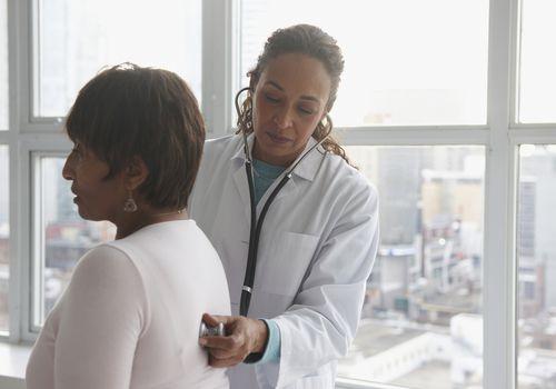 Doctor listening to patient's heart beat.