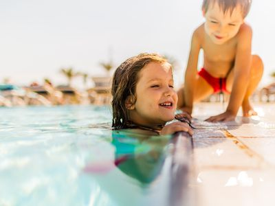 Two kids playing near a pool