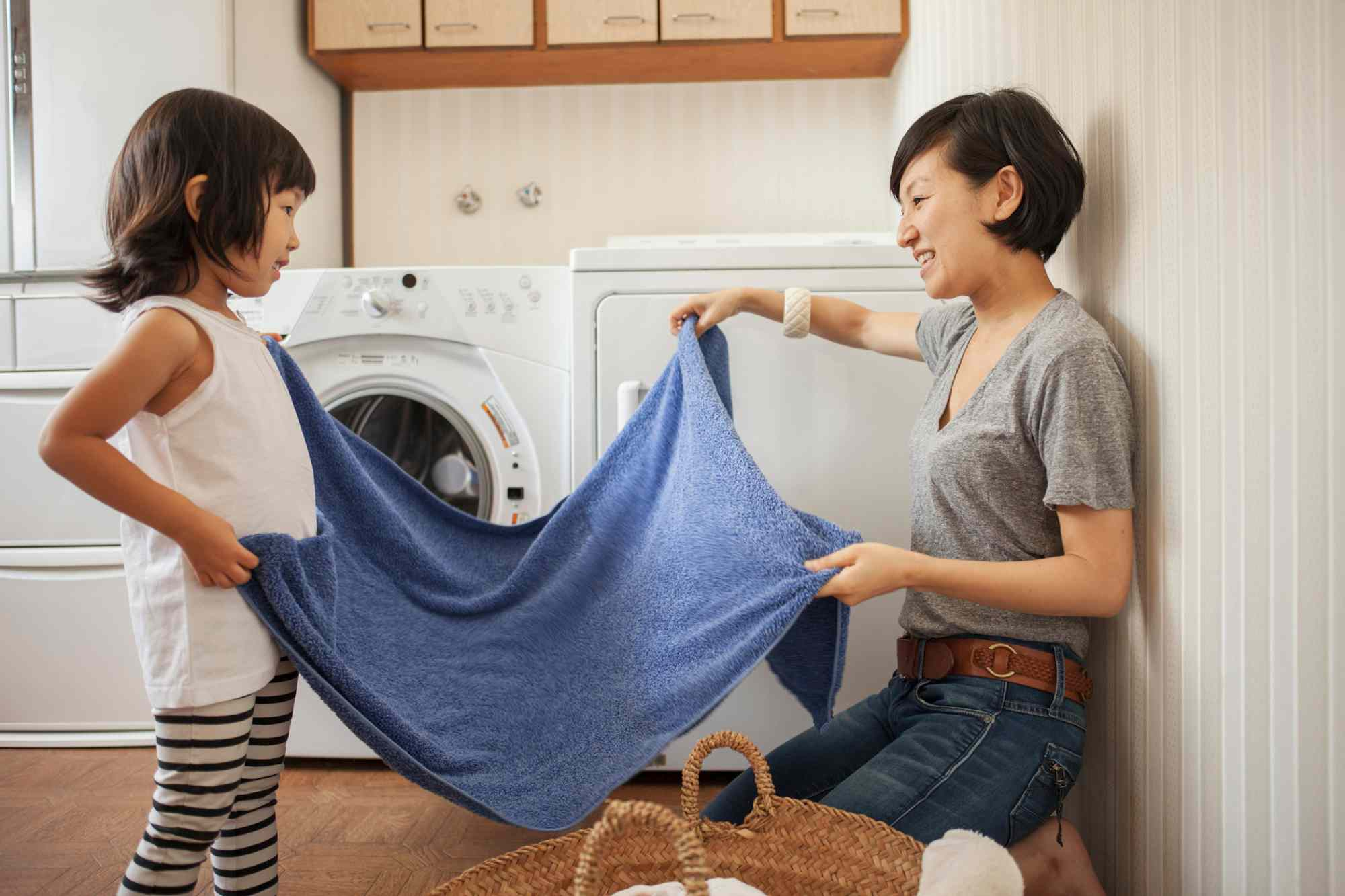 A child and her mother doing laundry together