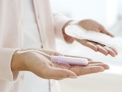 Woman holding tampon and pantyliner