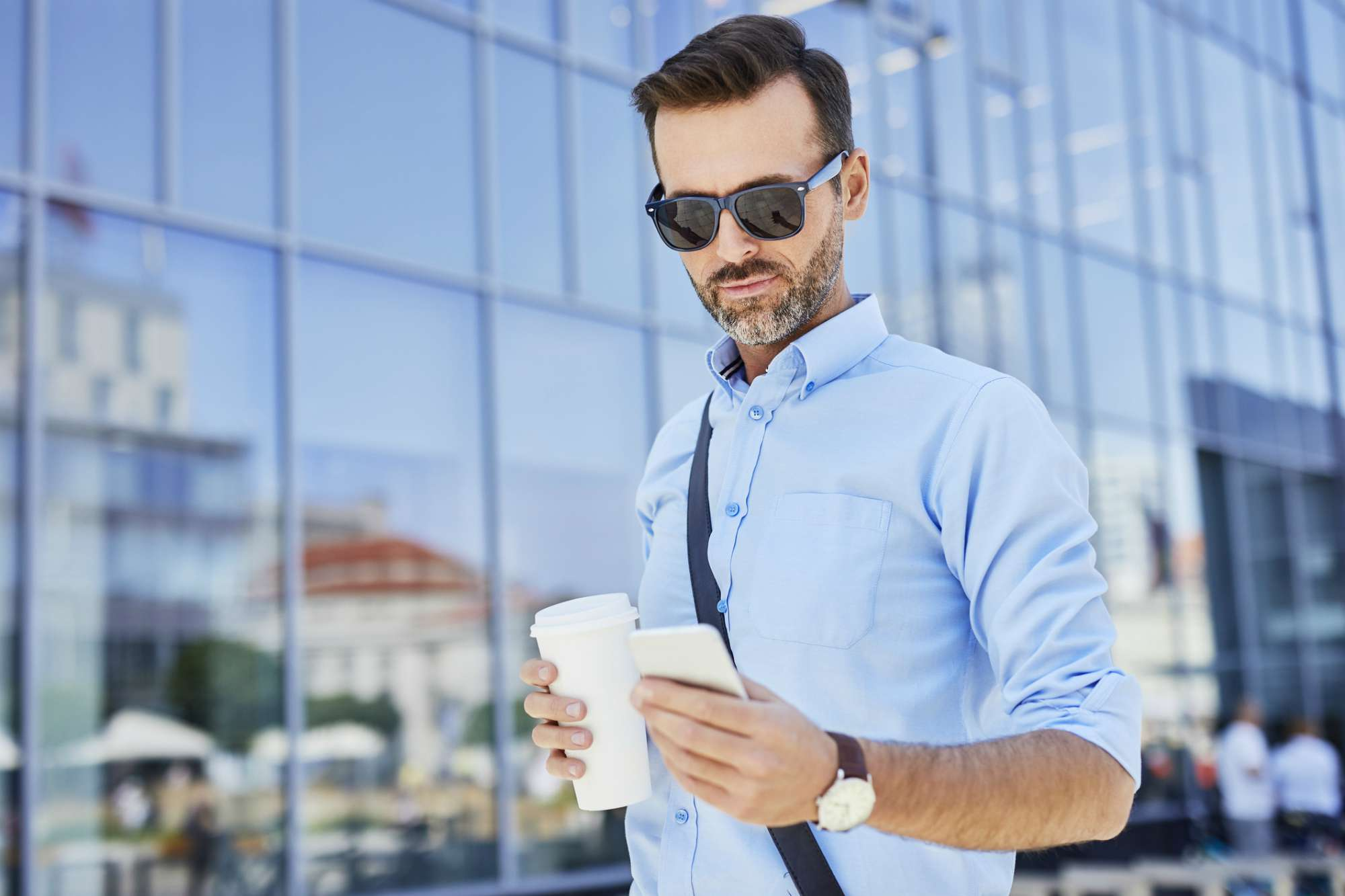 Man in sunglasses outside a glass building