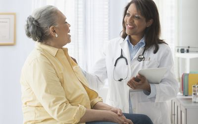 Woman talking to doctor in office