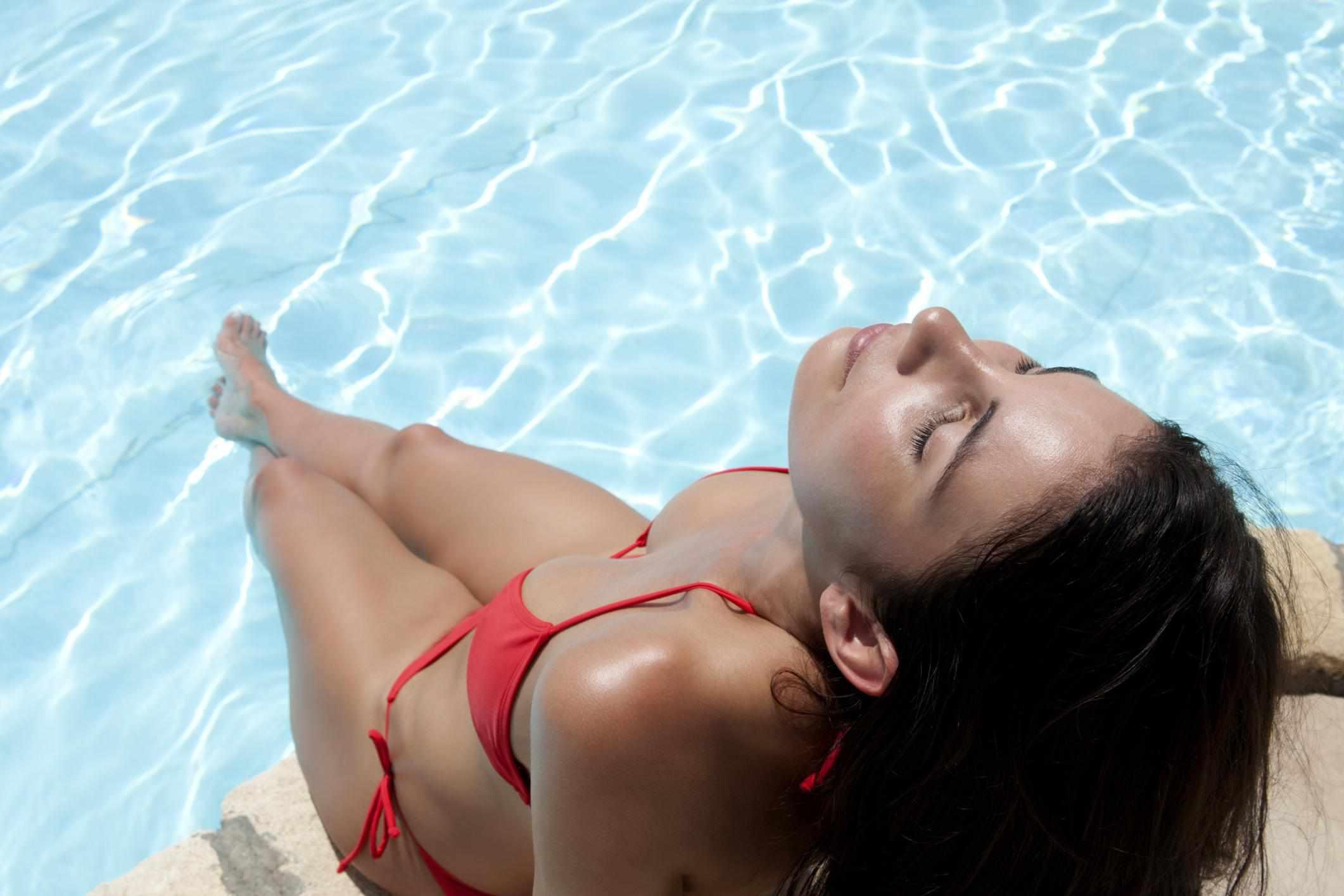 Young woman in bikini relaxing near pool
