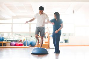 Male physical rehab patient standing on bosu ball