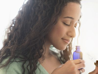 Close up of a woman smelling aromatherapy oil