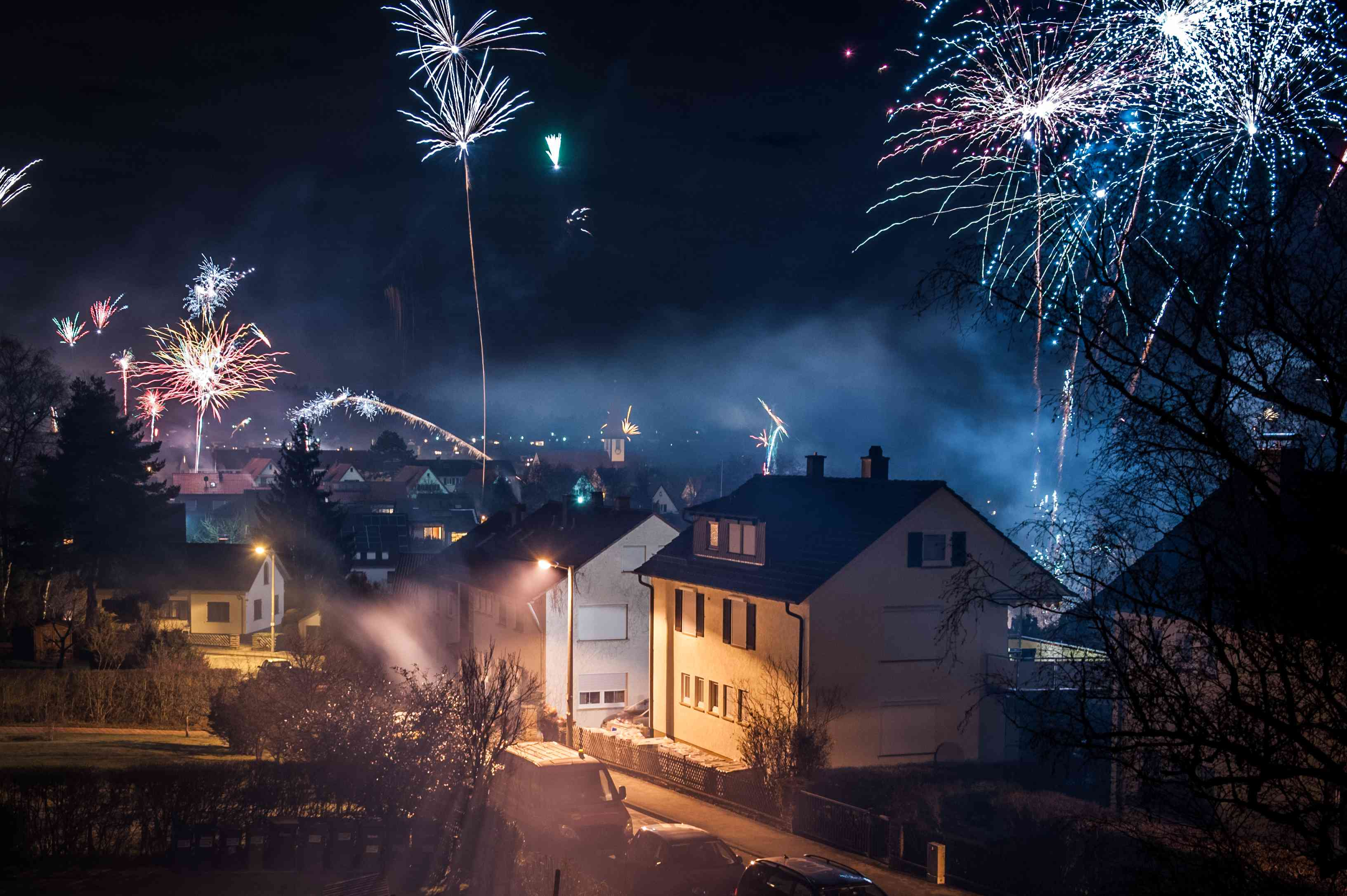 A neighborhood at night with fireworks in the sky