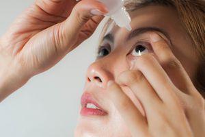 Woman inserting eye drops.