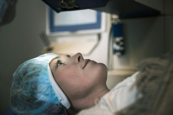 Patient undergoing laser eye surgery Female patient undergoing laser eye surgery at clinic