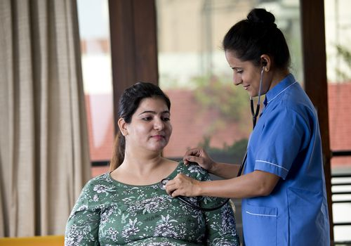 doctor examining overweight woman with stethoscope