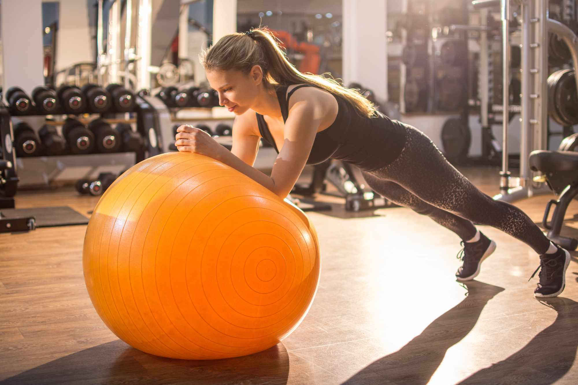 Woman doing plank exercise on exercise ball