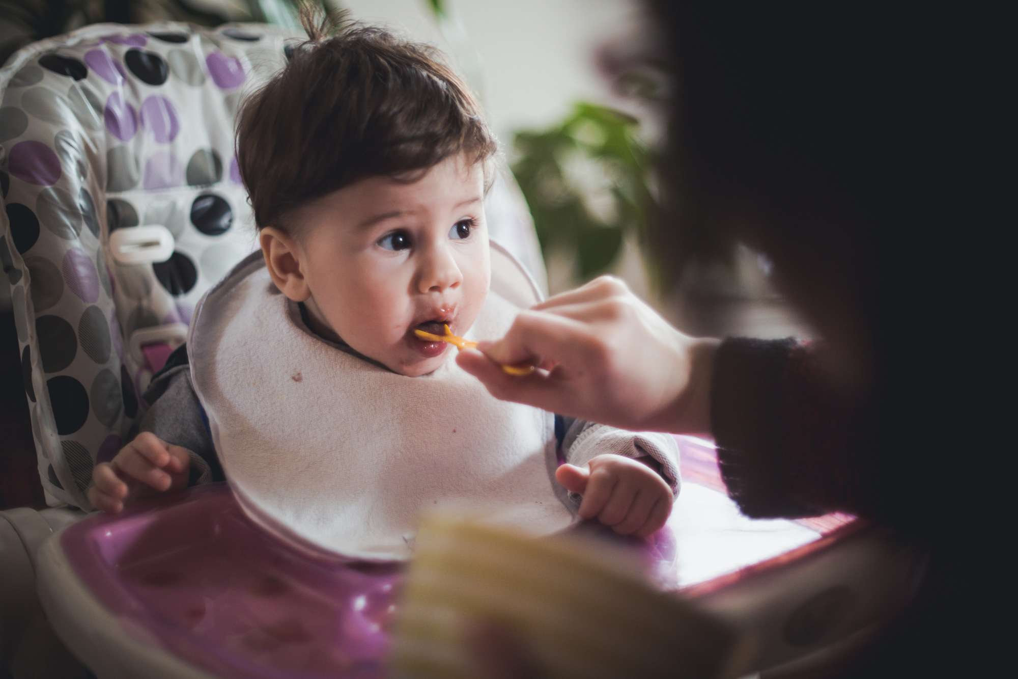 A baby being fed in a highchair