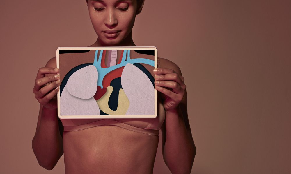 A woman holding a tablet over her upper chest that shows a depiction of internal organs.