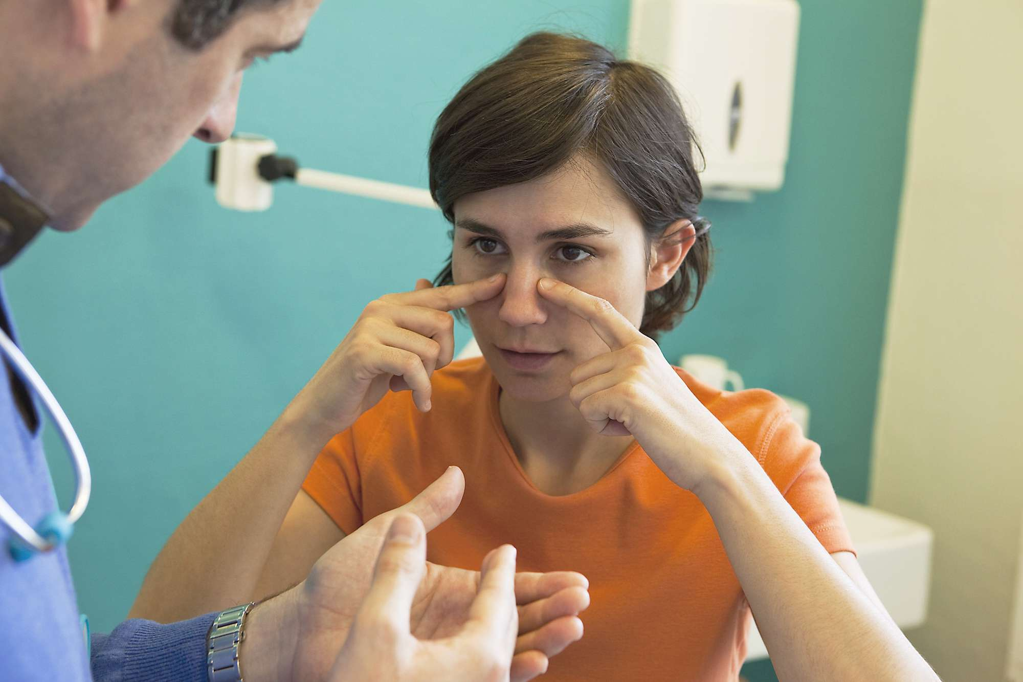 Woman touching her nose in discomfort talking with her doctor