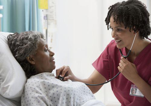 African nurse using stethoscope on hospital patient - stock photo