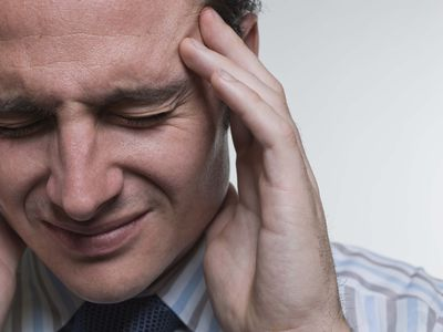 Man grabbing his head in pain