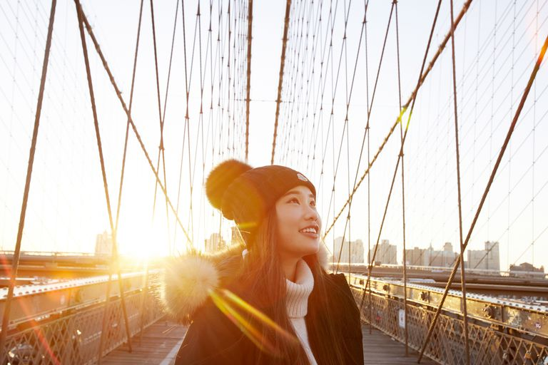 Woman in winter clothing smiling and looking up with sun in background on Brooklyn Bridge