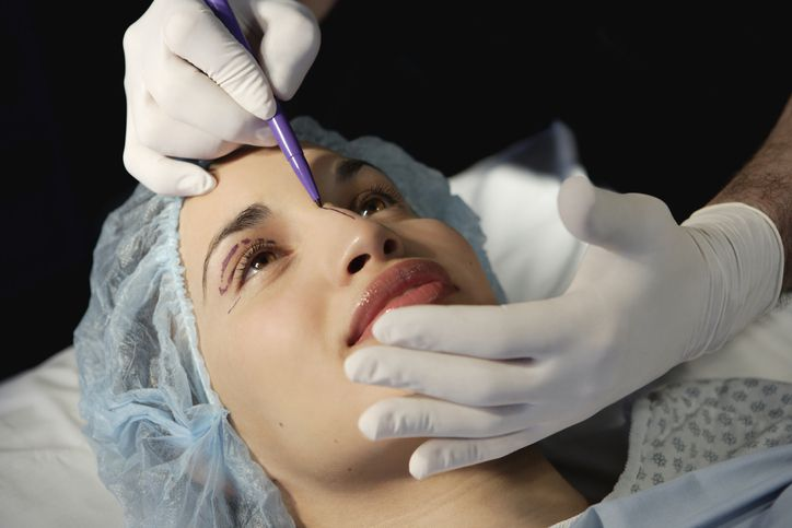 Preparing woman in surgical gown for facelift