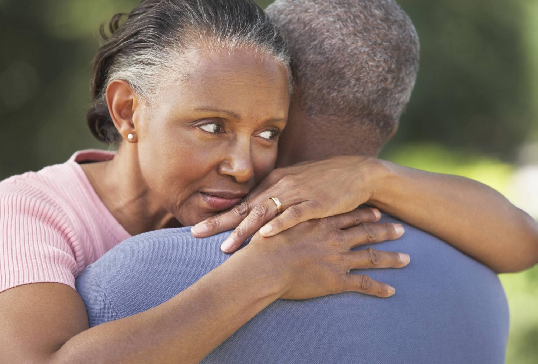 Senior woman embracing men, consoling, close-up