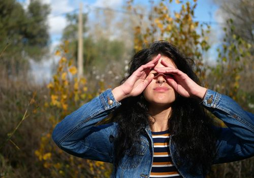 Young Woman Rubbing Eyes While Standing Against Trees In Forest