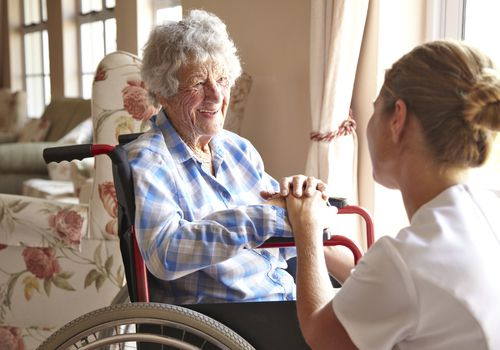 Elderly woman in wheelchair with nurse kneeling