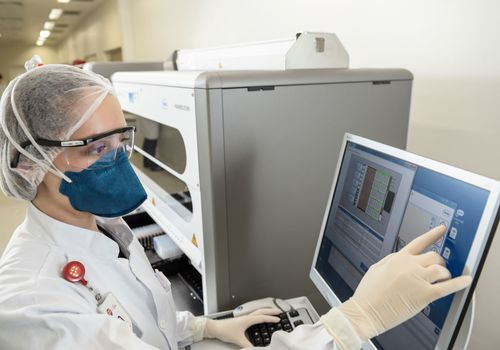 technician operating RT-PCR machine for COVID-19 tests