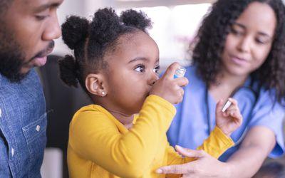 A Black girl using an inhaler, next to a Black doctor or nurse and a parent.