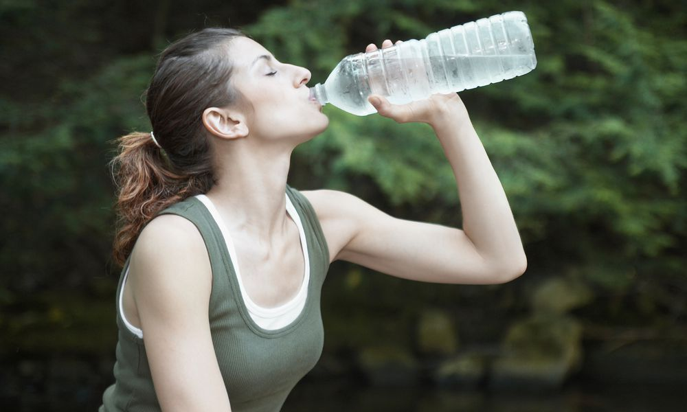 Young woman drinking bottle of water, outdoors, side view