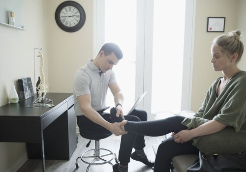 Photo of a physical therapist examining a woman's foot.