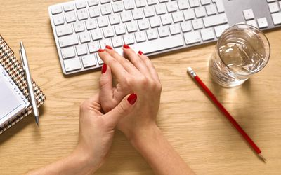 woman's hands - one holding the other in pain at a desk