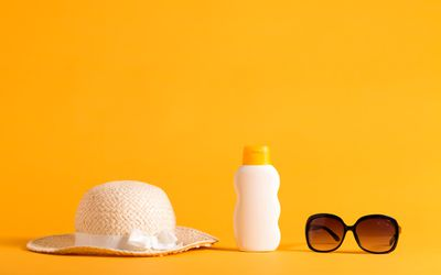 A sun hat, bottle of sun screen, and sunglasses on a bright orange background.