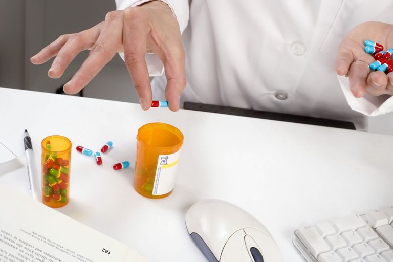 Compounding phamacist placing prepared pills in bottle