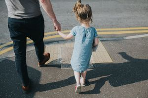 Child walking on the street holding father's hand.