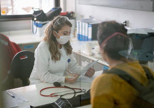 hospital worker wearing mask at desk