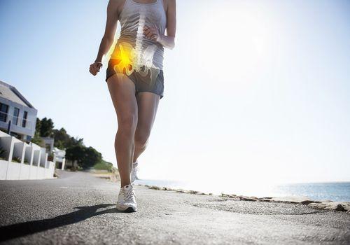 Woman running along coastline.