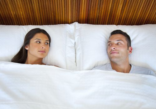 A couple lying in bed and looking at each other.