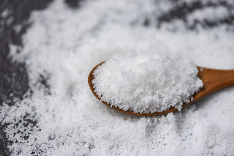 salt in a heaping pile and a wooden spoon