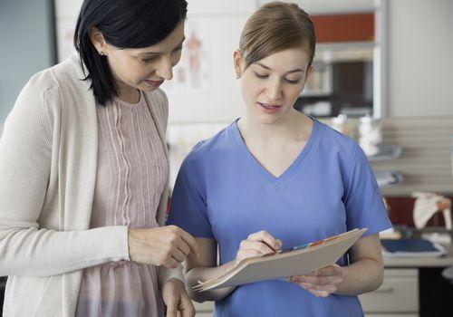 Woman asking nurse a question.