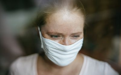 Woman looking out window with mask on.