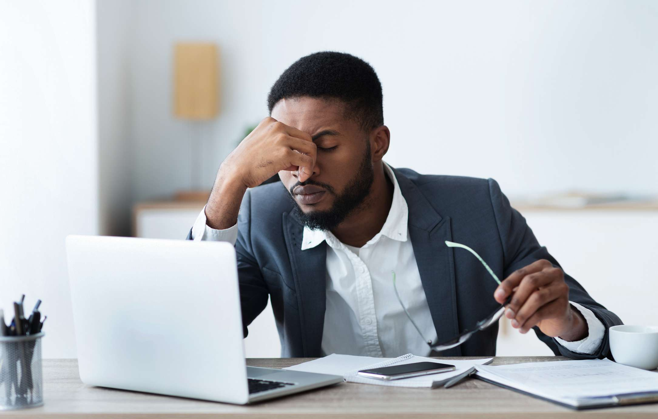 Man with a computer and phone holding glasses and experiencing eye strain.