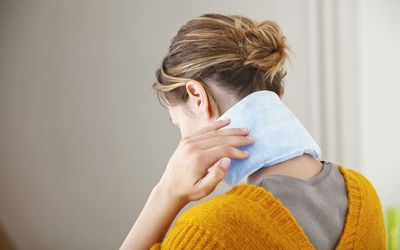 Woman with heat pack on her neck