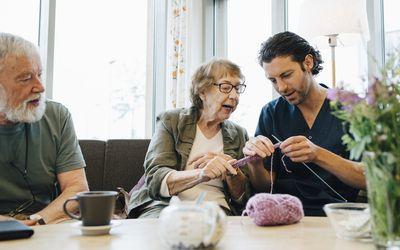 Retired senior woman teaching knitting to male nurse while sitting on sofa